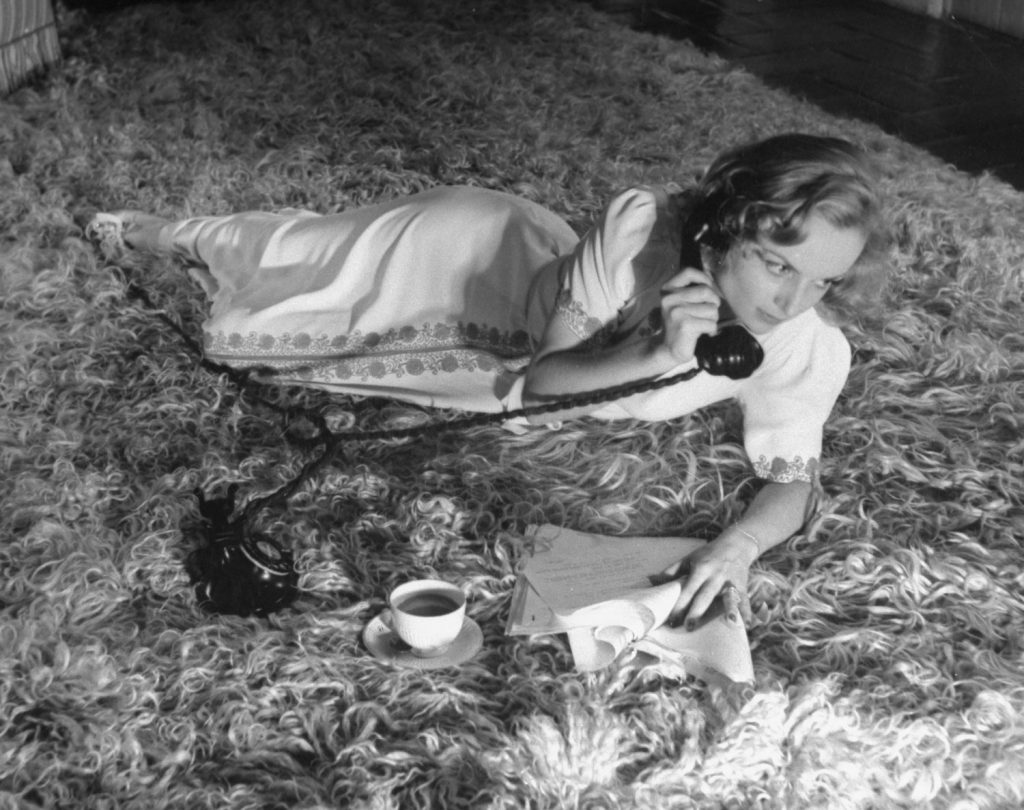 Carole Lombard drinks a cup of coffee and talks on the telephone while lounging on the floor of her Hollywood home in October 1939.