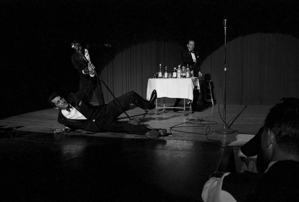 Dean Martin, Sammy Davis Jr., and Frank Sinatra pretend to be drunk on stage for a charity event in 1960.