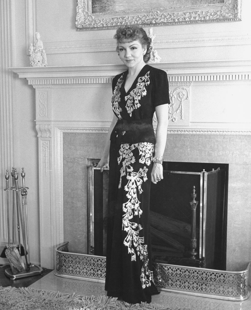 Oscar-winning actress Claudette Colbert poses in a two-piece evening dress in front of the fireplace in her home in Los Angeles' posh Holmby Hills neighborhood in 1939.