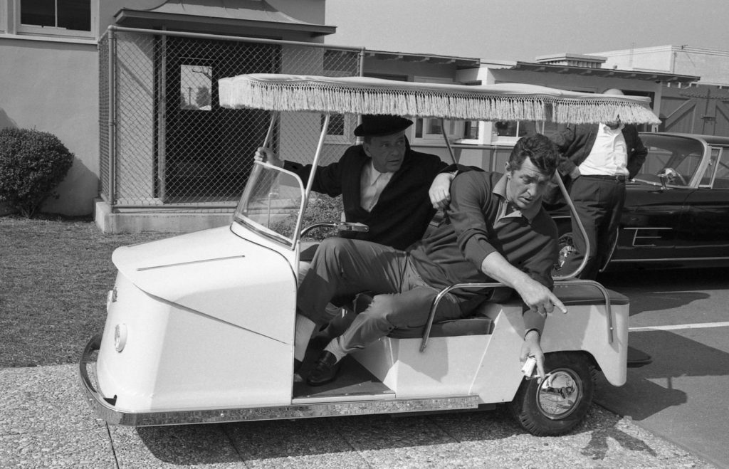 Frank Sinatra and Dean Martin drive a golf cart at Warner Bros. Studio in 1965 while making Marriage on the Rocks.