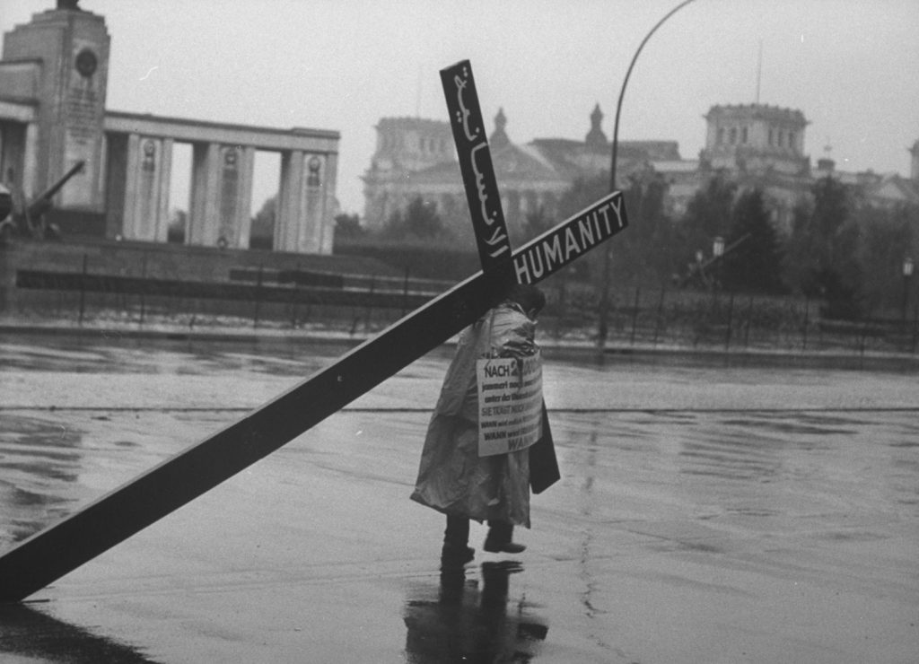 A Lebanese businessman carries cross in protest at the Berlin Wall