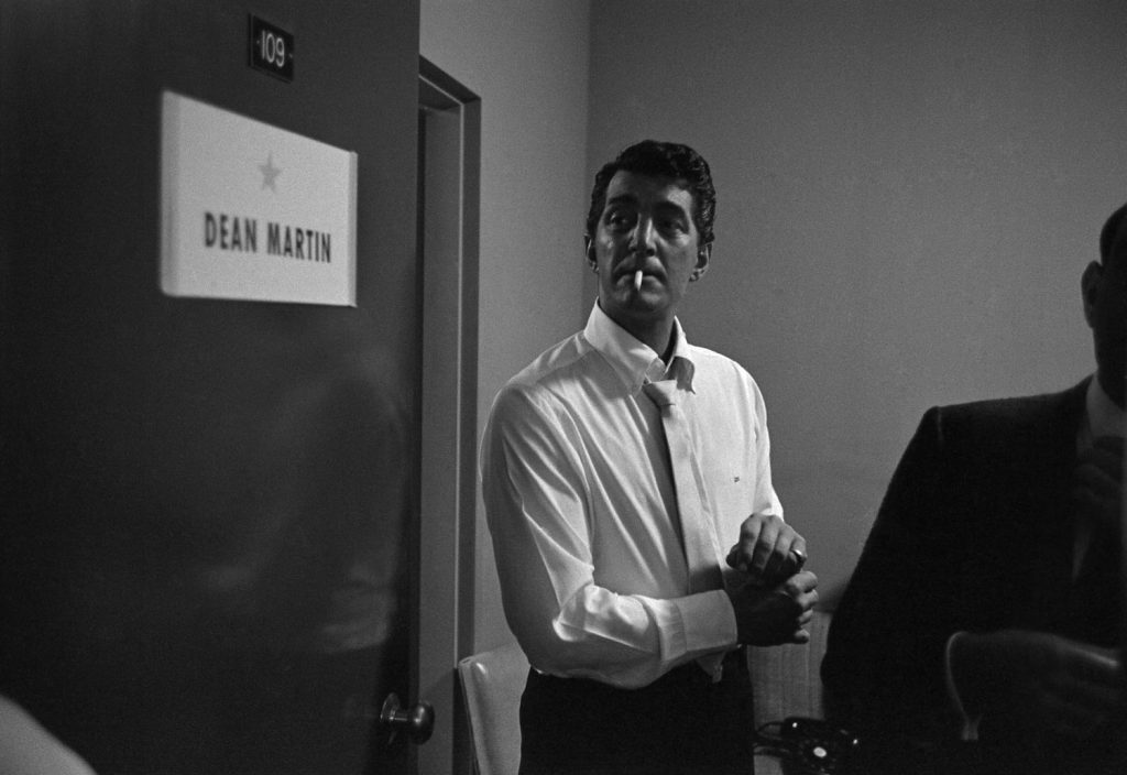 Dean Martin smokes a cigarette beside his dressing room door backstage before his performance in Las Vegas in 1958. He adjusts his cufflinks.
