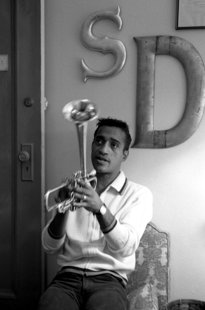 Sammy Davis Jr. plays with trumpet. The letters S and D hang on the wall behind him.