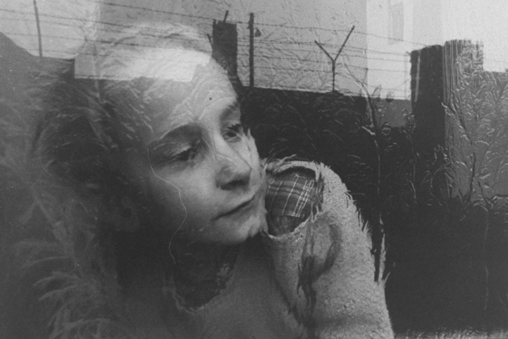 A girl looks through a frosty window at the Berlin Wall