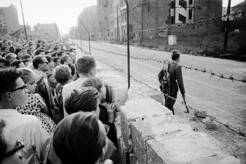 A crowd of West Berlin residents watch as an East German policeman patrols the Berlin Wall.