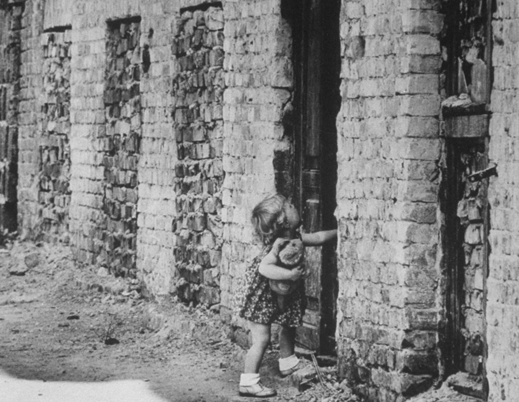 A West Berlin child struggles with a sealed door that has become a part of the Berlin Wall.