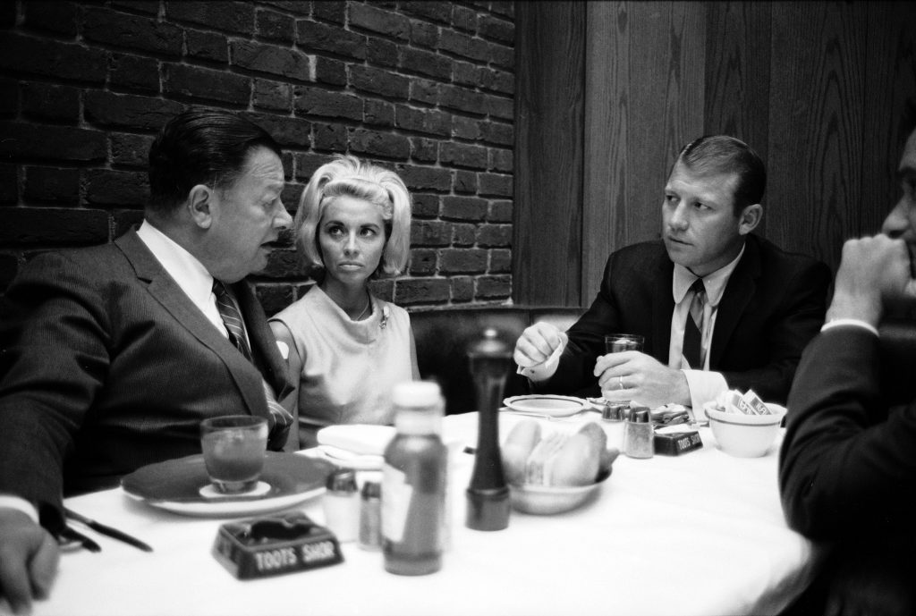 "Left to right, self-described ""saloon keeper"" Bernard ""Toots"" Shor talks with Merlyn Mantle and husband Mickey at Shor's restaurant, New York, NY, June 1965."