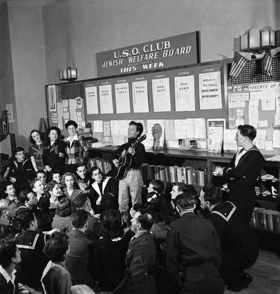 Woody Guthrie sings to sailors at a USO club, New York, 1943.