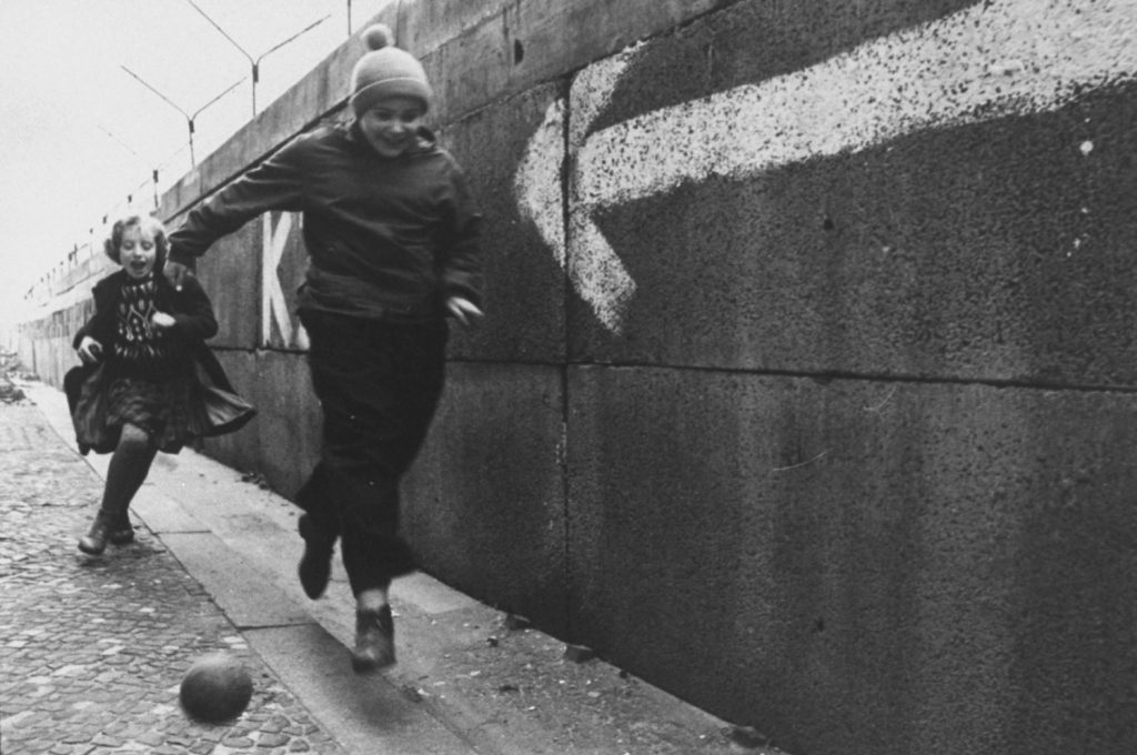 Children chase a ball beside the Berlin Wall