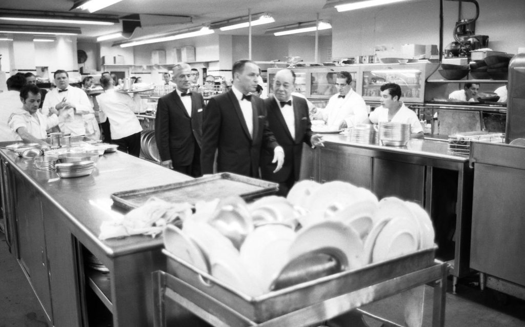Frank Sinatra and Joe E. Lewis walk through the kitchen to get to the stage at the Eden Roc Resort in Miami in 1958.