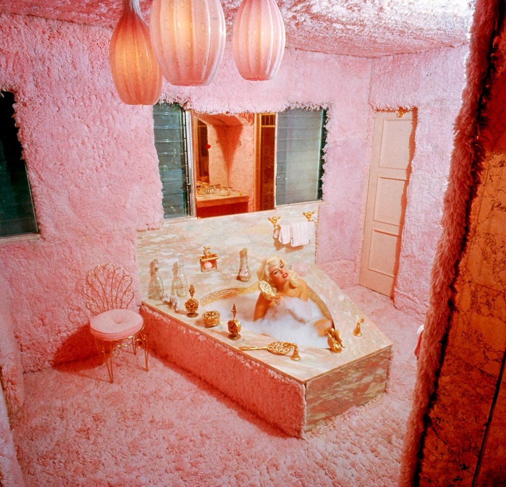 "Jayne Mansfield combs her hair while bathing in the pink carpeted bathroom of her home, known as ""The Pink Palace,"" in Los Angeles, 1960."