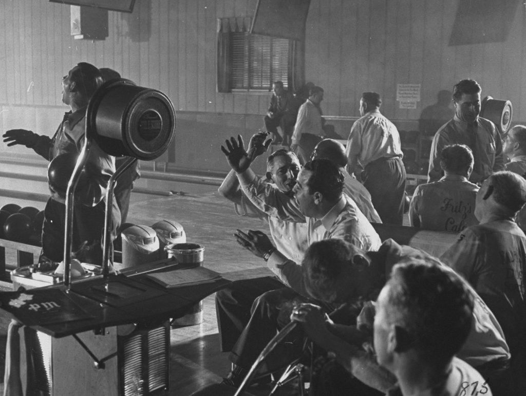 Men cheer a fellow team member's shot at a bowling alley.