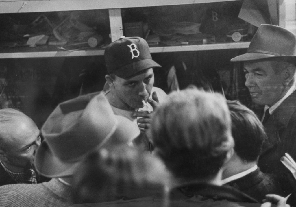 Brooklyn's Gil Hodges smokes and talks to the press in the locker room after a World Series game, October 1956.