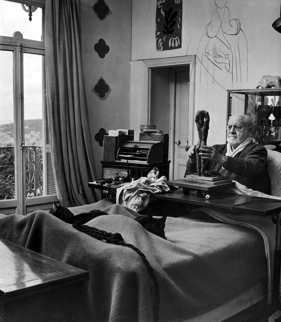 Henri Matisse (1869 - 1954) sculpts a nude female figure while sitting in bed in his apartment in 1951.