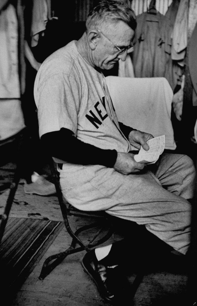 Yankees manager Casey Stengel reads in the locker room, September 1953..