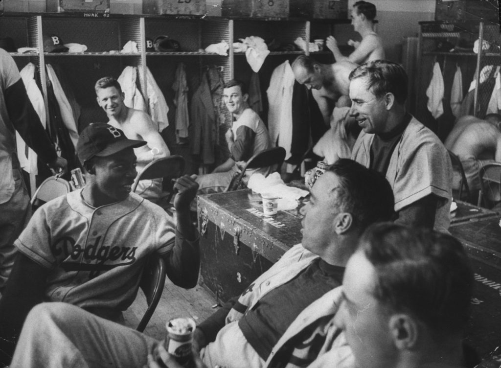 Sandy Amoros (with cap), Pee Wee Reese (on trunk), and Duke Snider (with beer) joke around after a game, May 13, 1955.