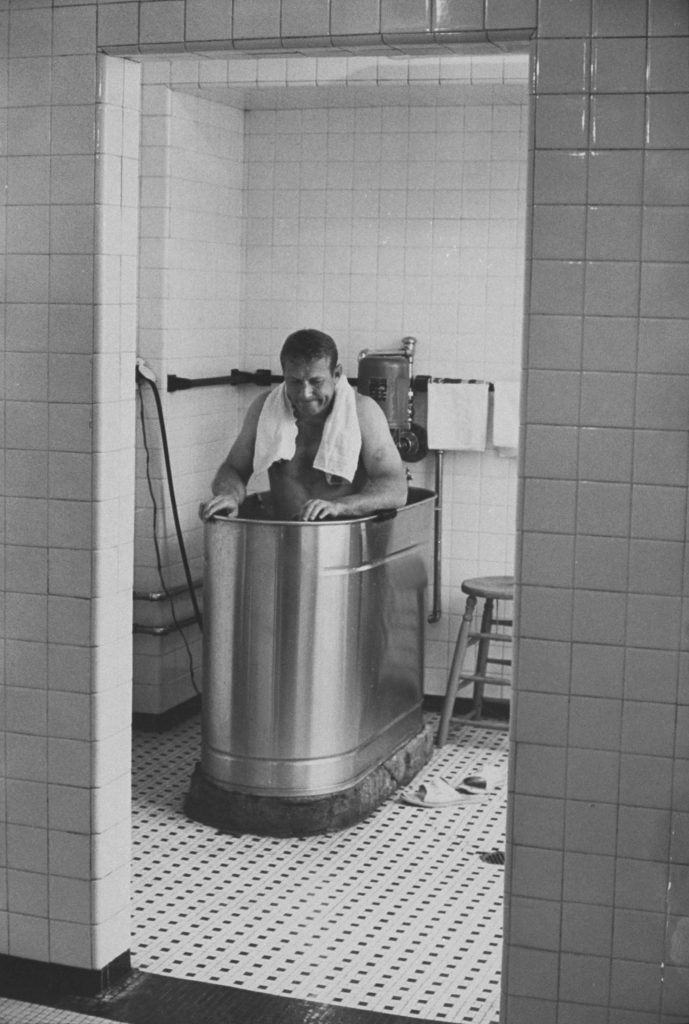 Mickey Mantle soaking in whirlpool bathtub after game, 1964.