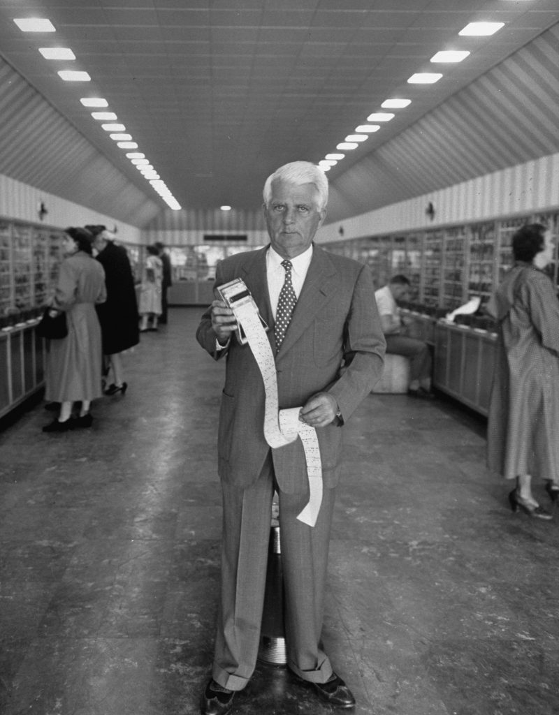Clarence Saunders stands with the ticker-tape technology at the heart of Keedoozle, his fully automated grocery store, Memphis, Tenn., 1948.