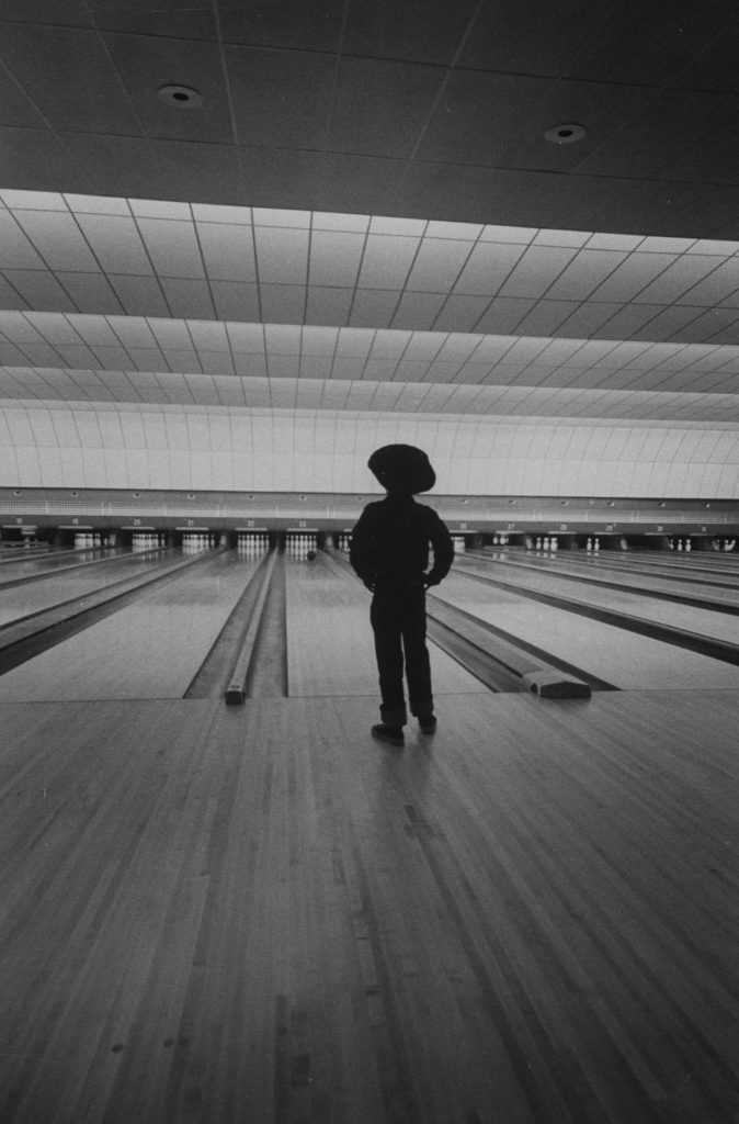 A bowler watches his ball approach the pins.