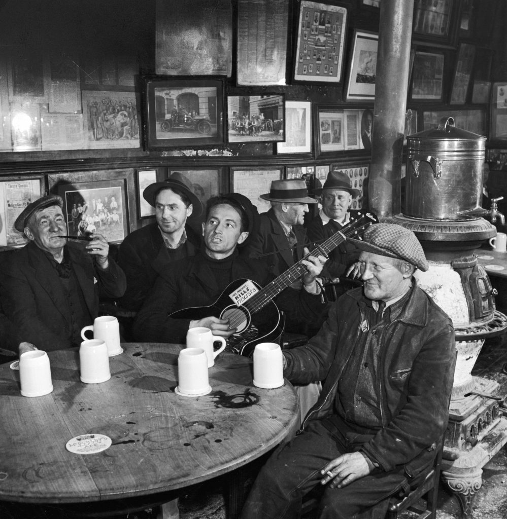 Woody Guthrie at McSorley's Old Ale House, still standing today in the East Village, New York City, 1943.