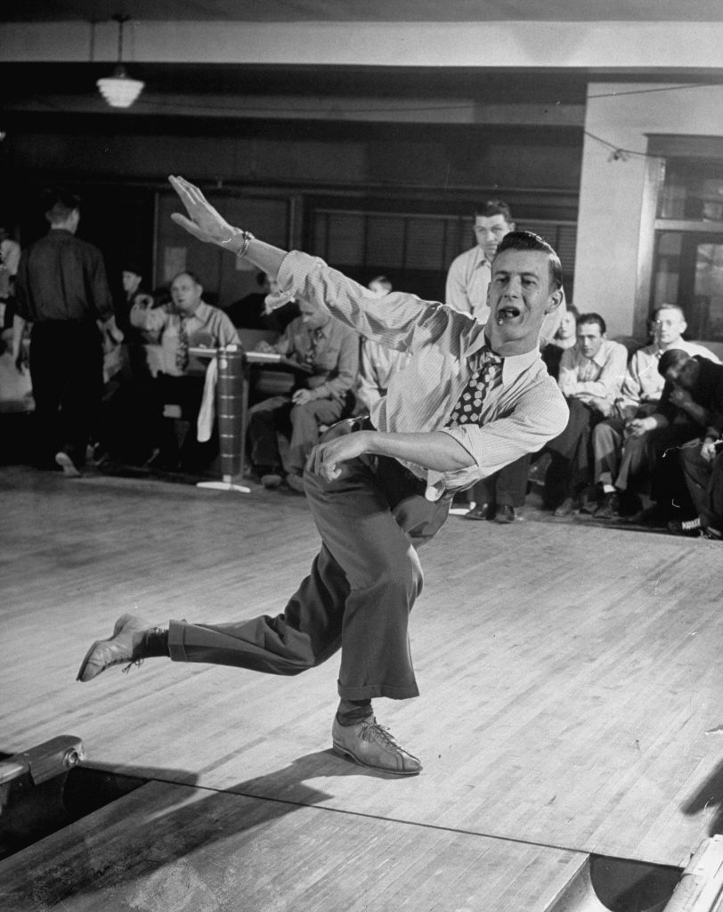 A man watches his ball roll down the lane with a cigar hanging from his mouth.