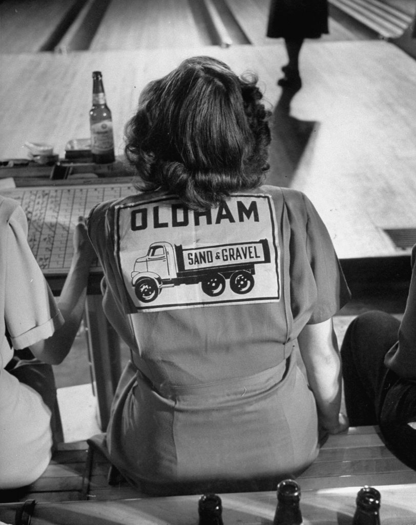 A female bowling team member wears a shirt representing her team and sponsor.