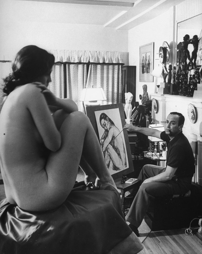 Jean Negulesco (1900 - 1993) paints a portrait of a nude model in his Hollywood studio.