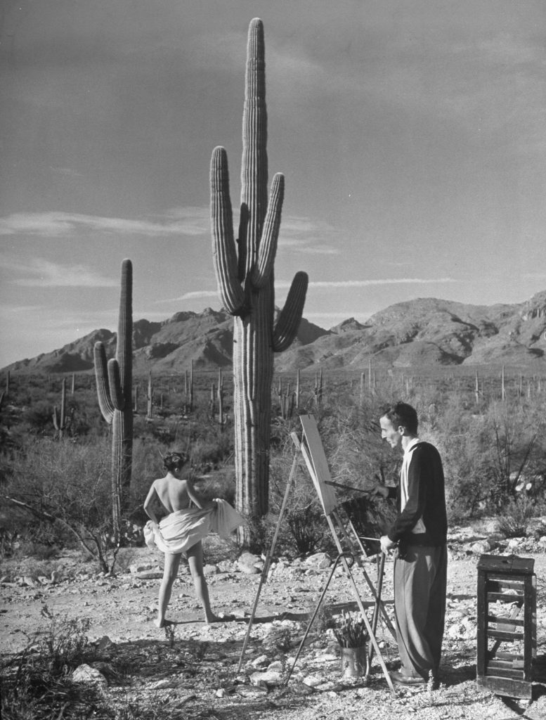 A nude model avoids cacti as an arthritis patient paints her in the American Southwest in 1948.