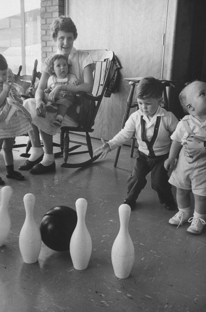 Children play with a plastic bowling ball and pins, provided in order to prevent them from interrupting their mothers as they bowl, at a nursery at the Hart Bowl