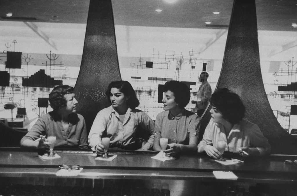Women at a bowling alley bar celebrate their high-scoring game with a round of drinks.