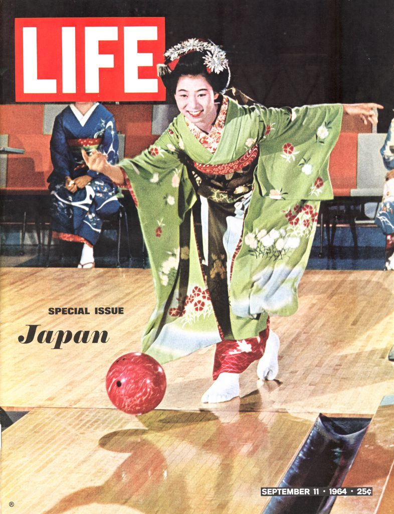 An apprentice geisha in a kimono and full make-up smiles as she bowls on a lane, watched by several other geisha in Kyoto, Japan.