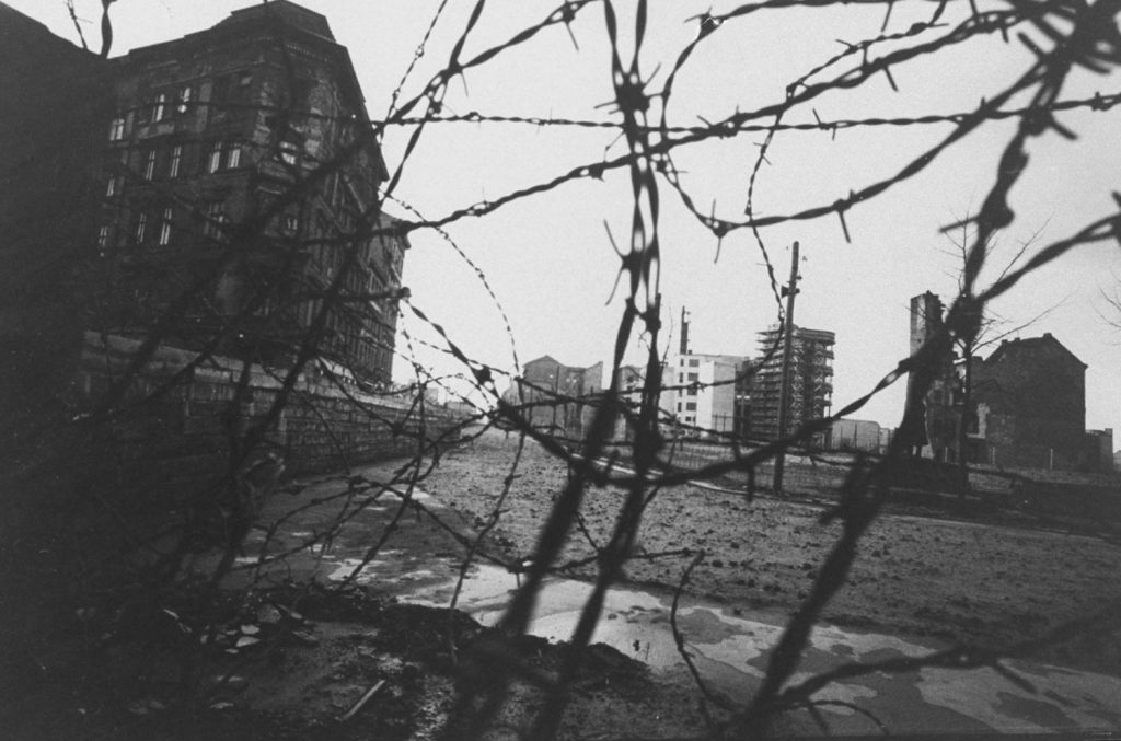 A divided Berlin is seen through a tangle of barbed wire.