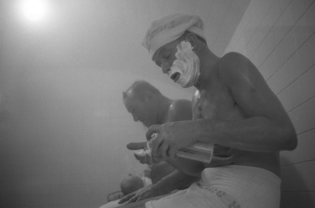 Frank Sinatra shaves in a steam room in Miami. He is wearing a towel around his waste and on his head. His face is covered with shaving cream.