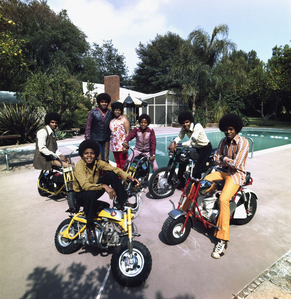 The Jacksons (clockwise left to right: Jackie, Marlon, Tito, Jermaine, and Michael) join parents Joe and Katherine in their backyard in Encino, California in 1970. Everyone is on a bike beside their pool.