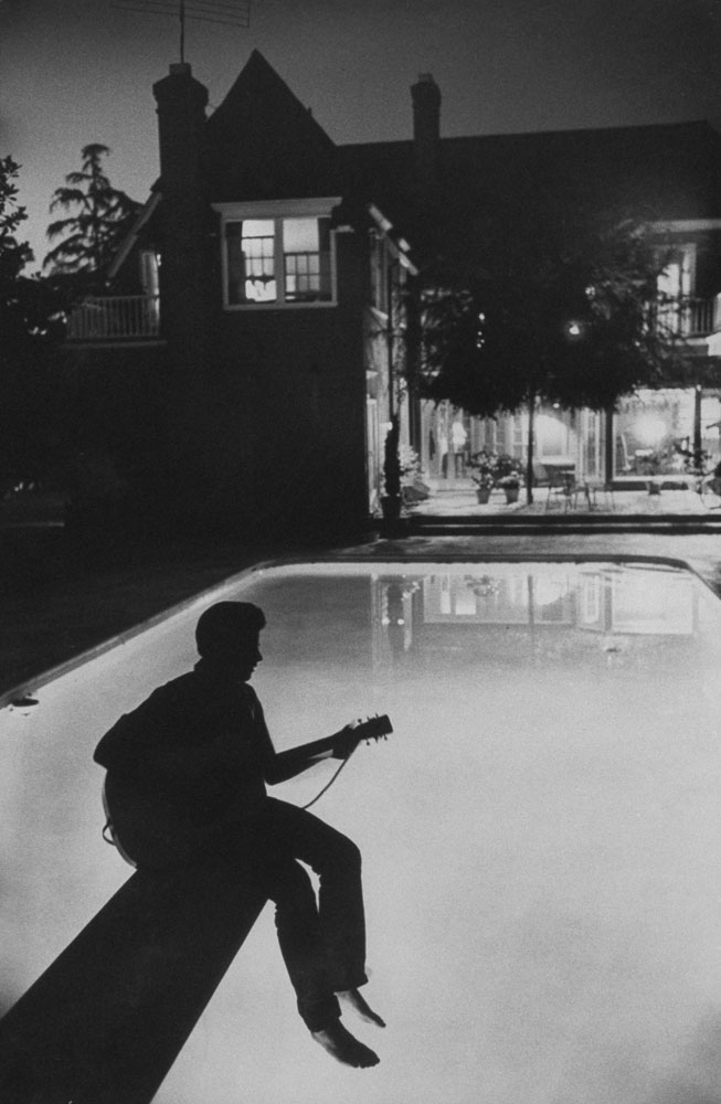 Ricky Nelson sits in shadow on the diving board of his family's pool in Hollywood in 1958.