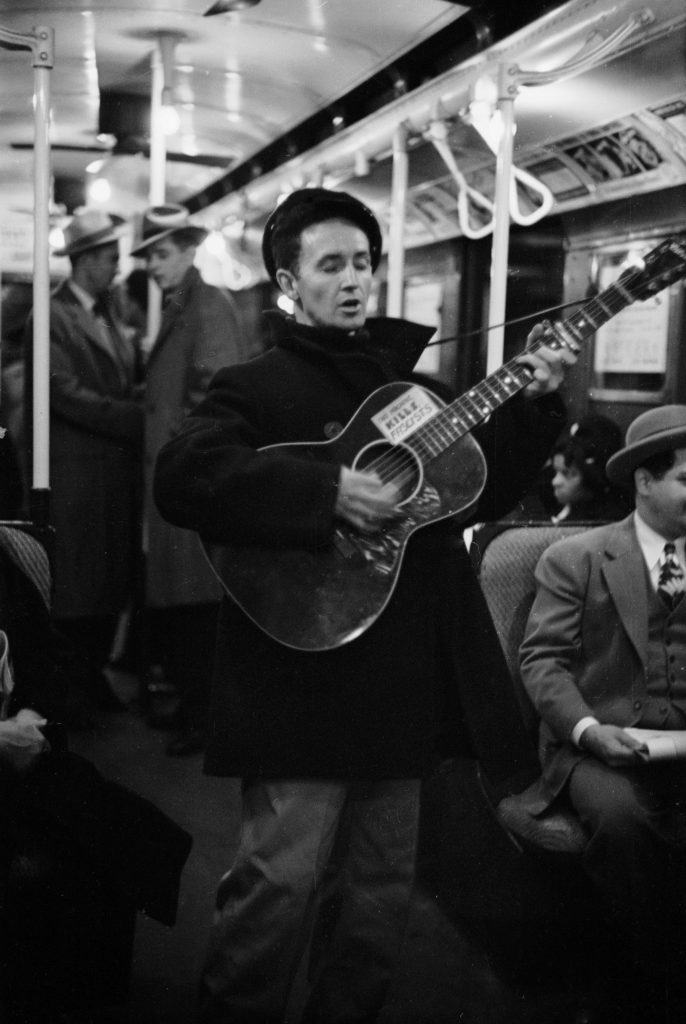 """Woody Guthrie entertains New York commuters in 1943, strumming a guitar bearing his now-famous slogan, """"This Machine Kills Fascists."""""""