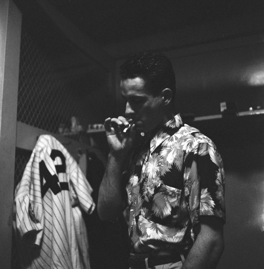 Jerry Coleman takes a long drag from a cigarette in the locker room of Yankee Stadium, New York, New York, April 1952, after learning that he has been called to active military duty for the Korean War. Coleman was a Marine pilot who had previously served in World War II.