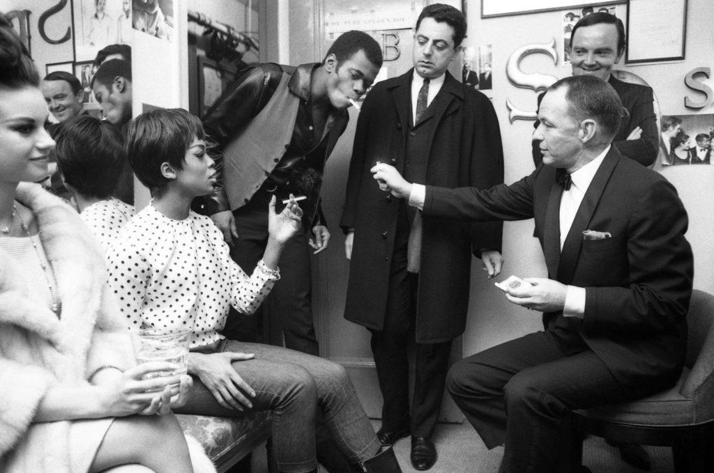 Frank Sinatra offers a light in Sammy Davis Jr.'s Golden Boy dressing room in 1964.