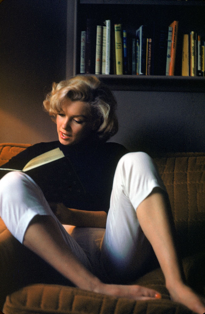 Marilyn Monroe Reads at Home. She is wearing a black shirt and white capri pants in 1953.
