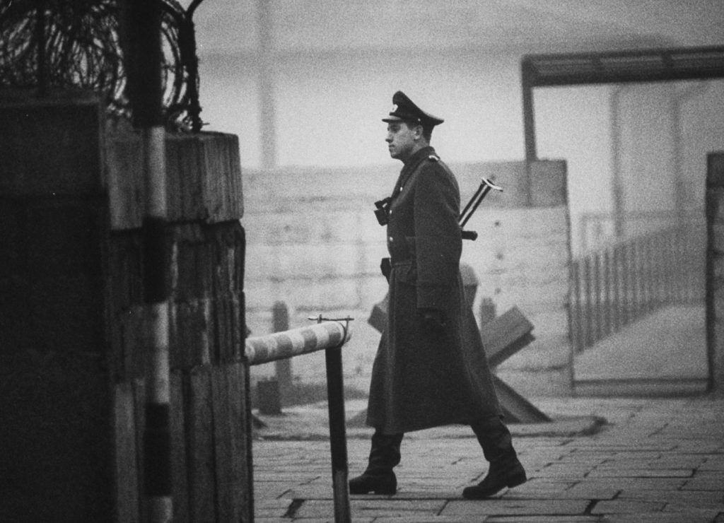 An East German policeman walks near Checkpoint Charlie in Berlin