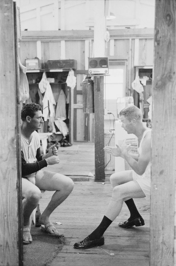 Ted Williams of the Boston Red Sox, left, talks with teammate Gordon Windhorn about batting in the locker room during spring training, Sarasota, Florida, 1956.