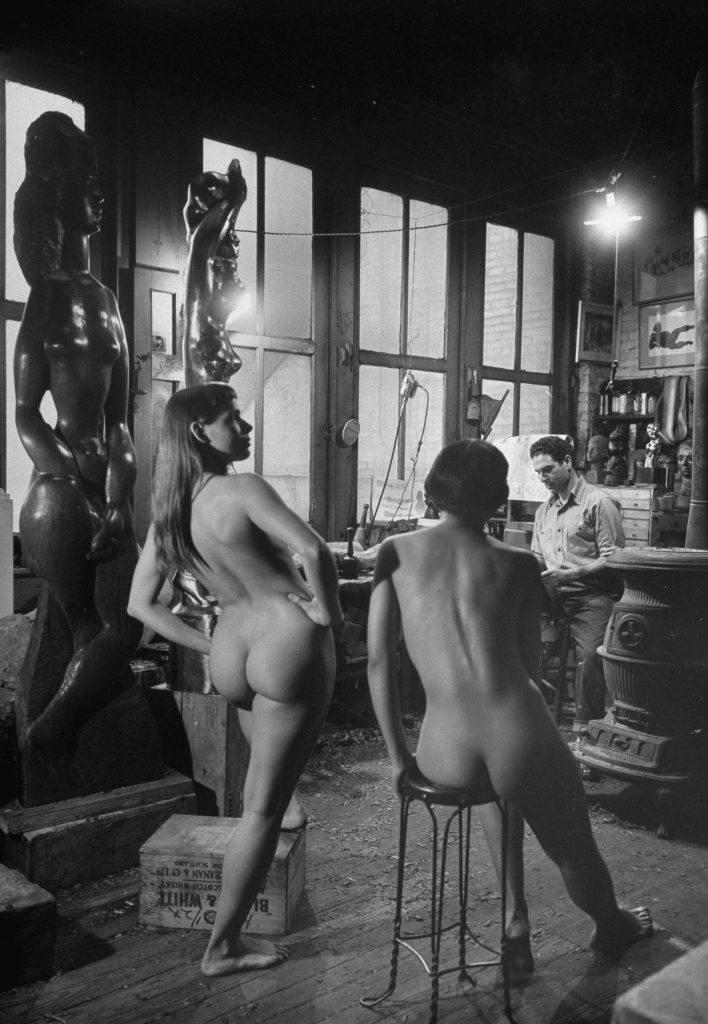 Sculptor Chaim Gross (1904 - 1991) works with a pair of models in his studio.