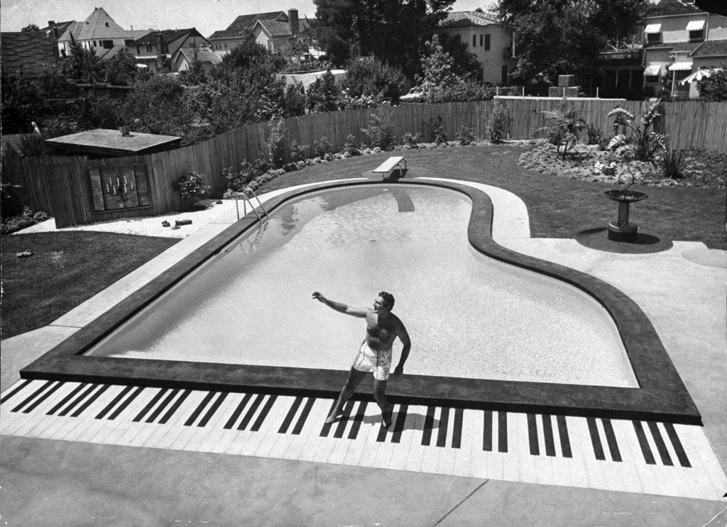 Liberace dances on top of the keys of his piano shaped pool in California in 1954.