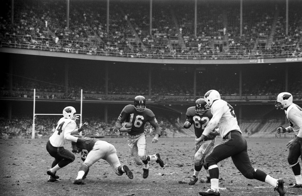 Frank Gifford carries the ball against the Cardinals as guard Darrell Dess (#62) runs interference.