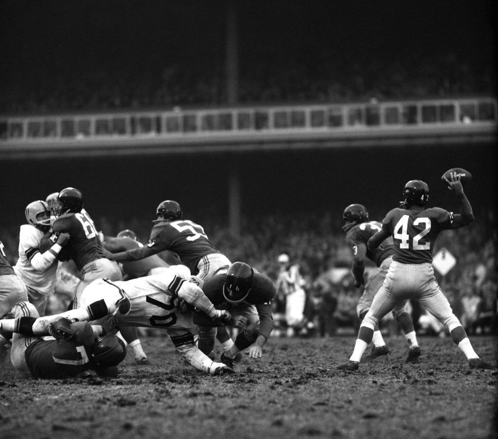 New York Giants quarterback Charlie Conerly drops back to pass during a game against the Steelers, 1960.