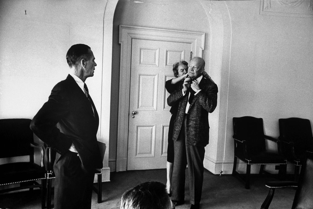 Eisenhower's secretary, Ann Whitman, helps the President with his borrowed tie.