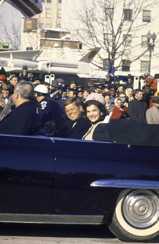 John Kenendy and Jackie Kennedy ride in a blue convertible through a cheering crowd during the Inaugural Parade.
