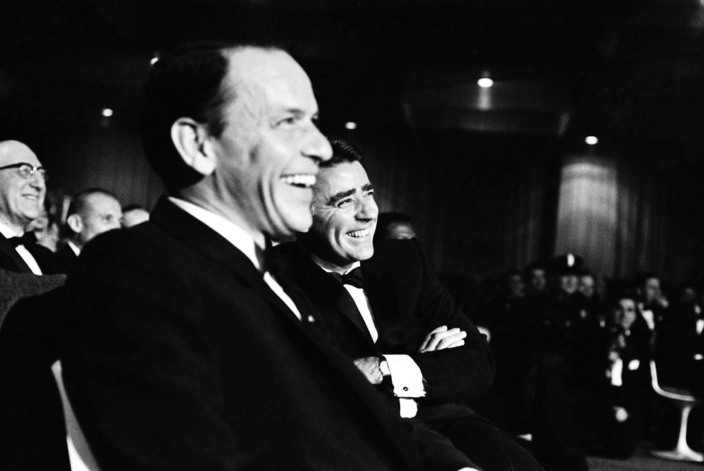 Frank Sinatra and Peter Lawford enjoy the entertainment of the Inaugural Gala.