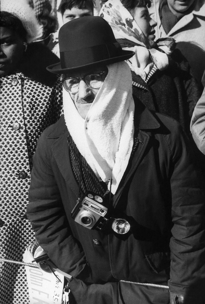 A spectator is seen bundled due to the harsh weather conditions during John Kennedy's inauguration.