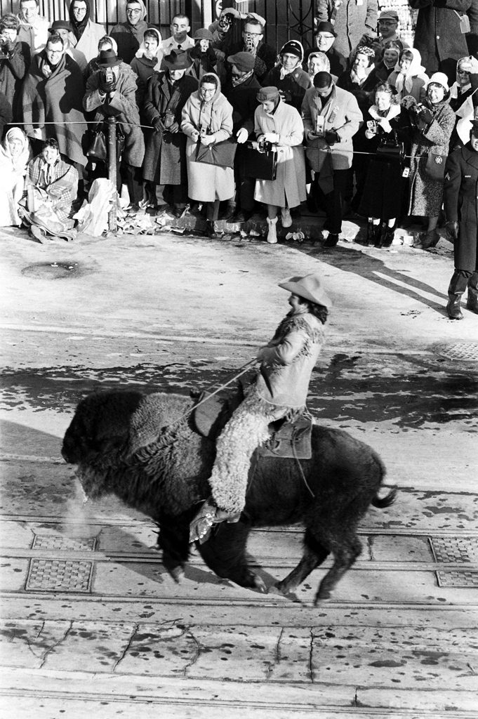 A man dressed like Buffalo Bill rides a bison during John Kennedy's inaugural parade down Pennsylvania Avenue.